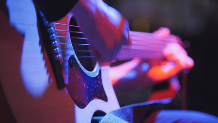 Musician in night club - guitarist plays blues acoustic guitar, extremely close up, telephoto
