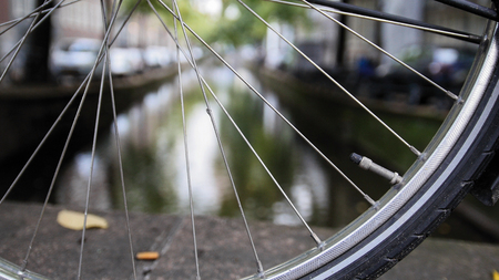 amsterdam canal: Details of bicycle wheel at Amsterdam canal, Autumn, Netherlands Stock Photo