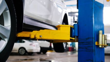Car in auto service lifting for repairing, mechanics in garage