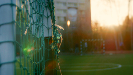 Teens play soccer across football goal at summer evening, de-focused background Stock Photo