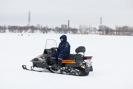 KAZAN, RUSSIA - JANUARY 19, 2017: Russian MoE lifeguard with snowmobile - rescuer on ice at winter day during Christs baptism holiday