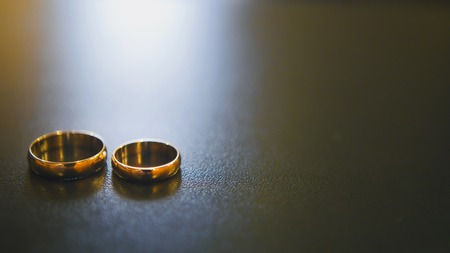 Golden wedding rings on table, close up Stock Photo