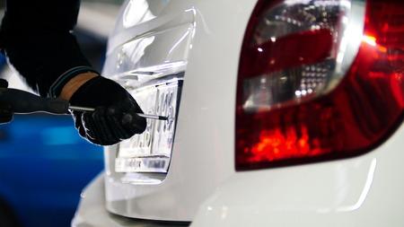 Monteur in de auto dienst doen van handmatige handelingen met de auto kenteken, tele
