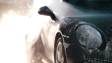 Worker in auto service is washing a luxury car by water hoses, backlight