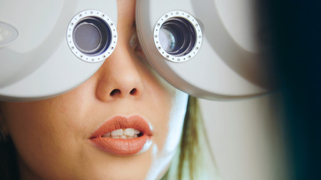Ophthalmology clinic - woman checks vision by modern equipment - eyes exam, close up