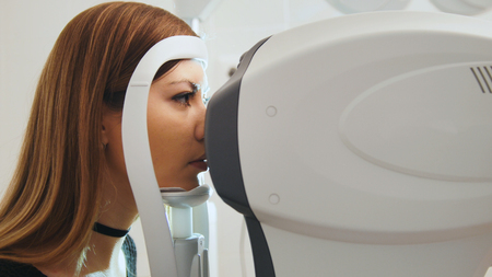 Ophthalmology clinic concept - young attractive female doing checking vision by modern electronic technology