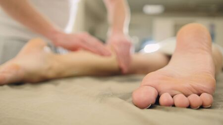 Massage for foot and legs in spa salon - relaxation therapy, cosmetic and healthcare concept