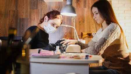 Nail master in medical mask doing professional manicure for white caucasian model, cosmetic salon