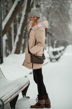 Young pretty girl in winter park stands on snow-covered alley