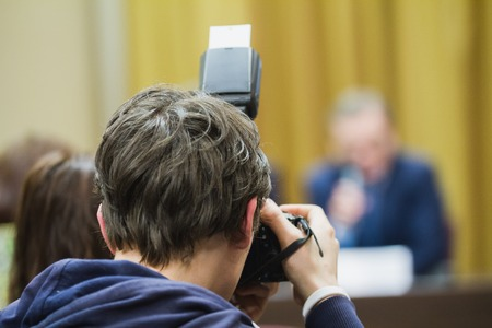 Photographer at press conference - telephoto close up Stock Photo