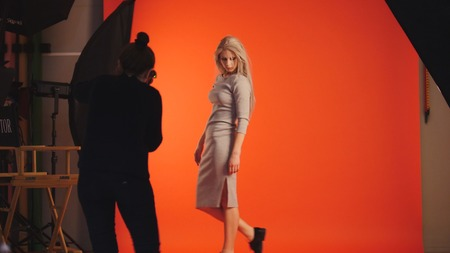 Blonde girl posing for photographer - model stands near red background Stock Photo