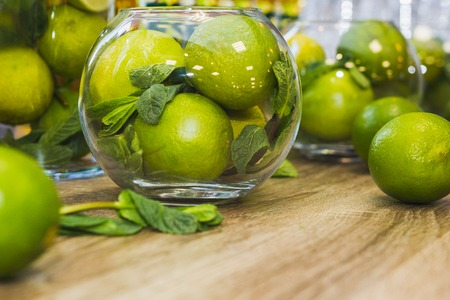 Green fruits - Limes with mint on wooden table