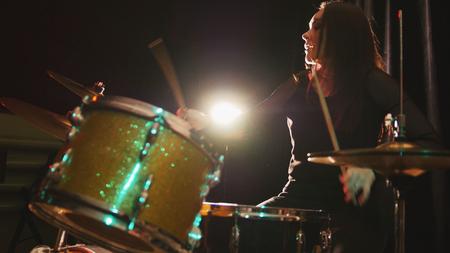 down beat: Gothic black hair girl percussion drummer perform music break down - teen rock music Stock Photo