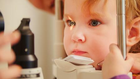 Childs optometry concept - little girl checks eyesight in eye ophthalmological clinic Standard-Bild