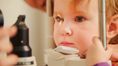 Childs optometry concept - little girl checks eyesight in eye ophthalmological clinic Banque d'images