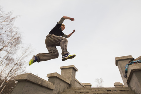 Wide angle view - parkour jumping in winter snow park - free-run training
