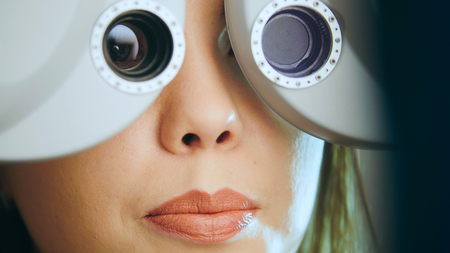 Ophthalmology concept - young woman checks the eyes on the modern equipment in the medical center Stock Photo