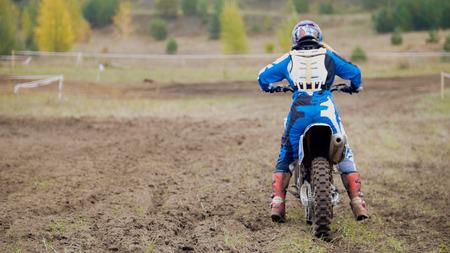 Motocross racer start riding his dirt Cross MX bike - rear view Stock Photo