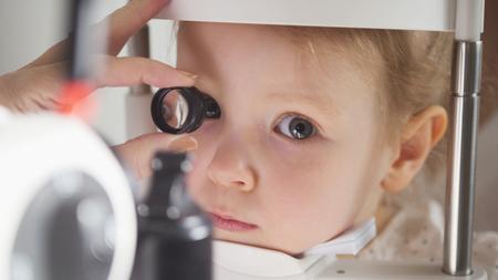 Childs ophthalmology - doctor optometrist checks eyesight for little girl