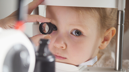 Childs ophthalmology - doctor optometrist checks eyesight for little girl