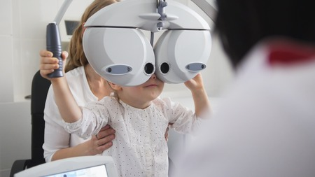 Children ophthalmology - optometrist Checks Eye of little girl
