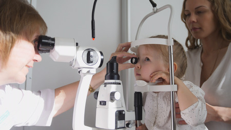 Optometrist checks little girls eyesight - mother and child in ophthalmologist room Banque d'images
