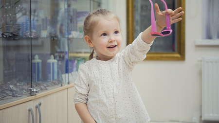 Adorable child blonde girl in ophthalmology clinic chooses new eyeglasses in glasses store Stock Photo