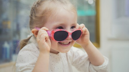 Portrait of child in glasses - blonde girl tries fashion medical glasses shopping in ophthalmology clinic Stock Photo