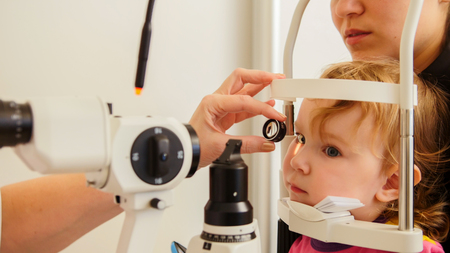 Optometrist checks girls eyesight - mother and child have consultation in ophthalmologist room