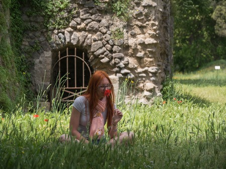 Red hair woman in green grass in pompeii, Italy - hot summer midday Stock Photo