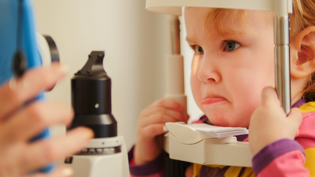 Childs optometry - little girl checks eyesight in eye ophthalmological clinic - close up