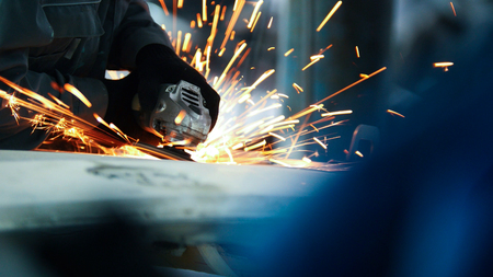 stuff: Car service - worker grinding metal construction with a circular saw