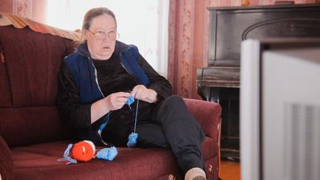 Old lady home at sofa - senior woman watching television and knits wool socks Stock Photo