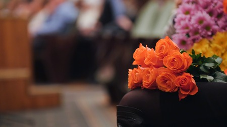 Audience in the concert hall holding flowers and applauding the performance on stage