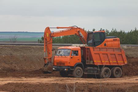 Heavy excavator loading dumper truck on road construction among fields
