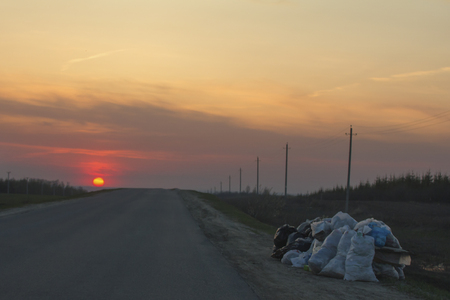 Garbage dump along the road at sunset - ecology concept