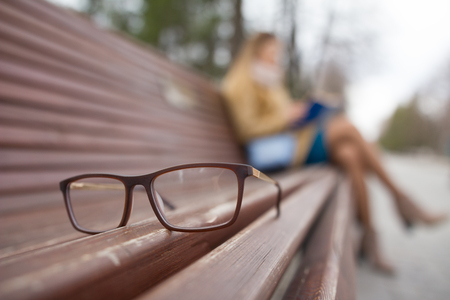 Ophthalmology lifestyle concept - glasses and de-focused reading girl