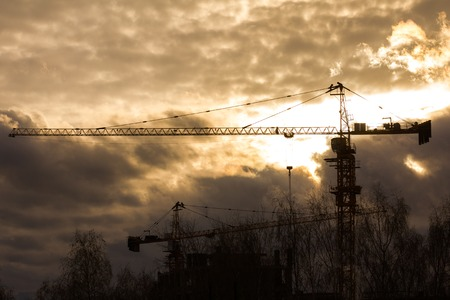 Construction cranes in front of sunset - silhouette
