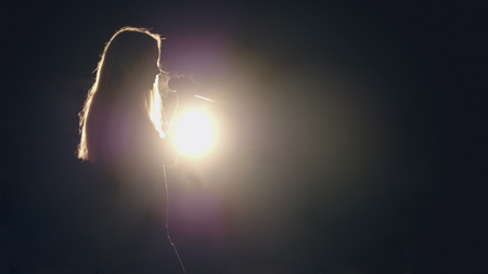 A woman sing in microphone at scene in front of bright lantern - silhouette
