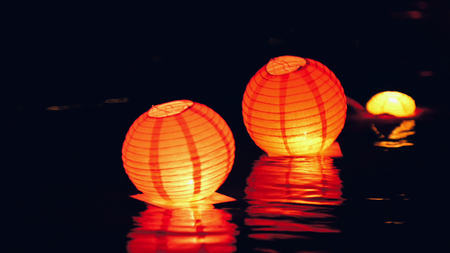 Circle floating lighting Lanterns on river at night - romantic festival Stock Photo
