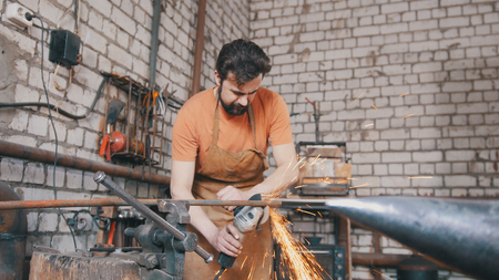 forge: Beard man blacksmith forging an knife with circular saw
