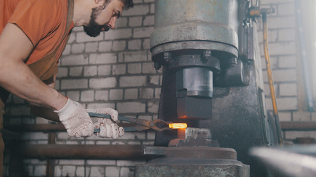 forge: The blacksmith treats the metal part under the hard pressure Stock Photo