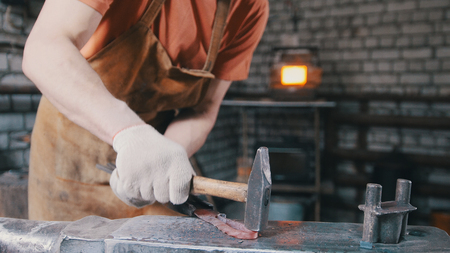forge: The smith gives shape with a hammer to a red-hot metal object