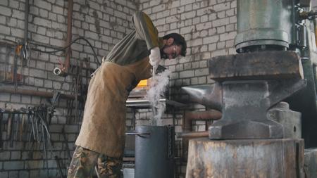 hot temper: Blacksmith manually temper steel knife in engine oil Foto de archivo