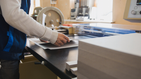 sheet of paper: Print operator pulls printed sheet of paper Stock Photo