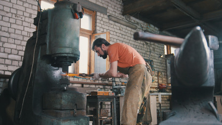 forge: Man blacksmith forges the metal at the mechanical hammer