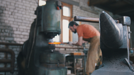 smithy: Blacksmith substitutes a metal piece for an automatic hammer Stock Photo