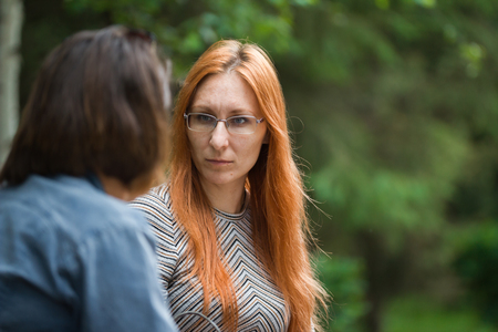 Portrait of a woman who talks to her girlfriend while sitting on a bench Stock Photo