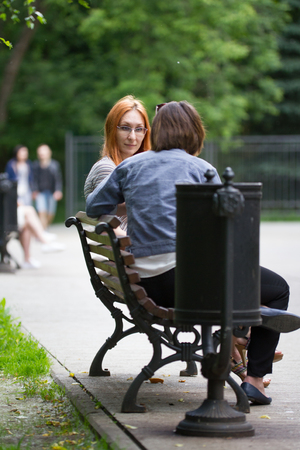 A girl in glasses sits on a bench next to a girlfriend Stock Photo