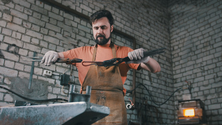 forge: Muscular blacksmith in forge hammering steel products